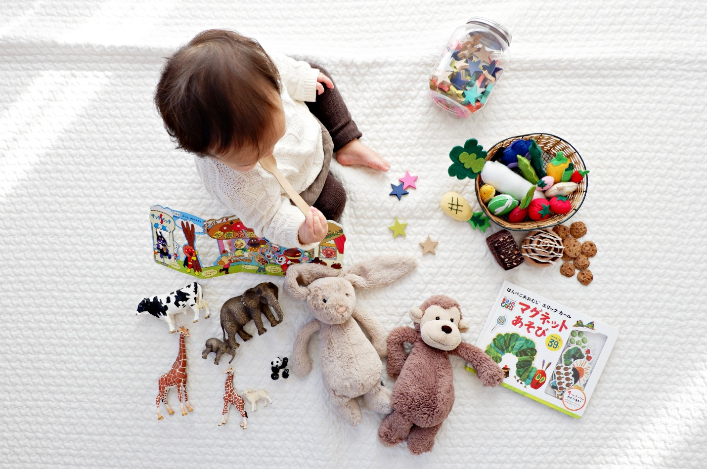 baby surrounded by a variety of toys